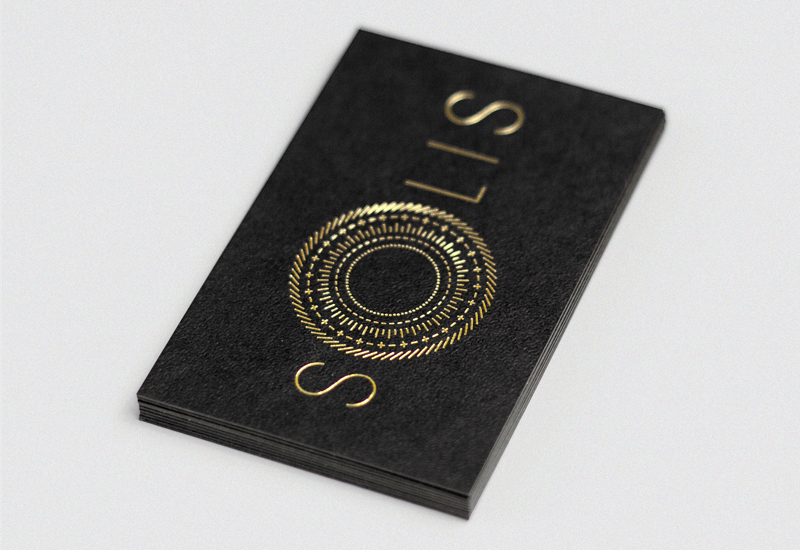 Sans-serif logotype and business card with gold foil print finish and embossed surface finish designed by Richard Baird for fashion label Solis