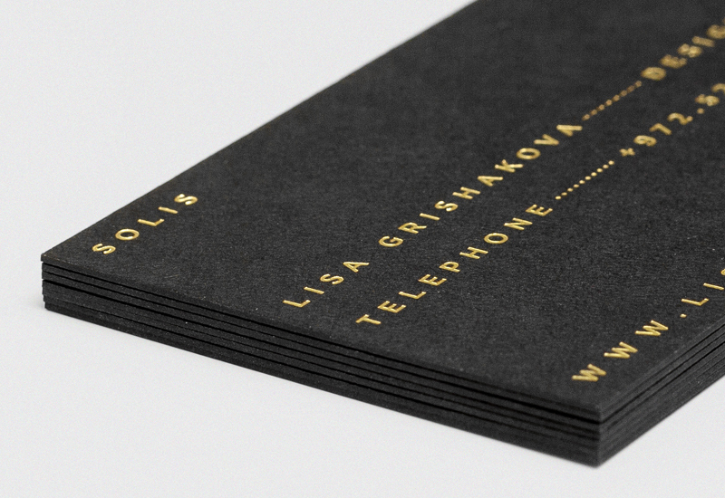 Sans-serif logotype and business card with gold foil print finish and a Colorplan sandgrain embossed surface finish designed by Richard Baird for fashion label Solis
